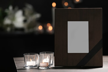 Funeral photo frame with black ribbon and burning candles on table in dark room