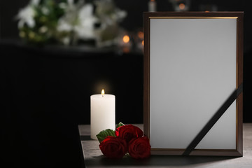Funeral photo frame with black ribbon, roses and burning candle on table in dark room