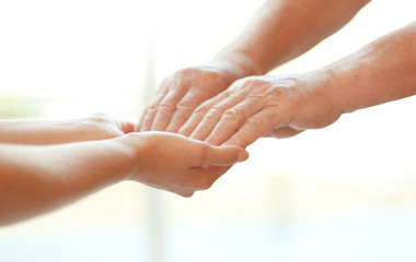 Young woman holding elderly man hands on blurred background, closeup. Help service