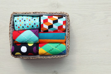 Fototapete - Box with colorful socks on wooden background, top view