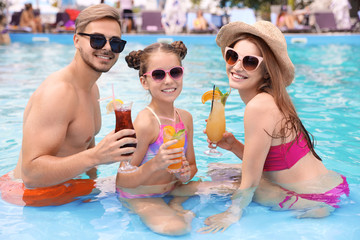 Happy family with cocktails in pool on sunny day