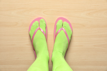 Woman wearing bright socks with flip-flops standing on floor, top view