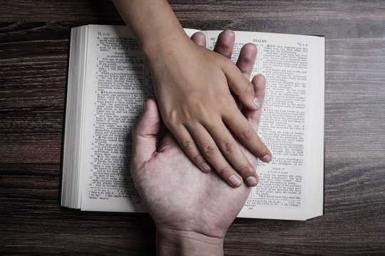 Child and Man Hands On The Bible