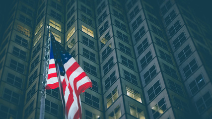 USA flag in front of business building at night, business and economy concept