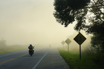 Highway in the morning fog, with motorcycle