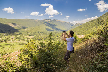 Guy taking photo with smartphone of beautiful landscape