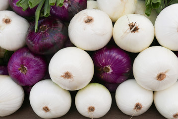 Purple and white onions stacked at the farmers market creating an overall background