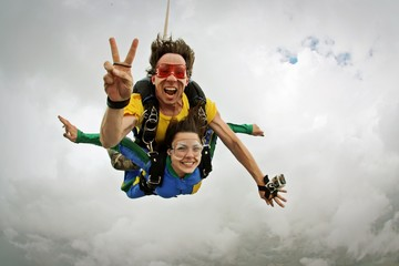 Skydiving tandem happiness on a cloudy day