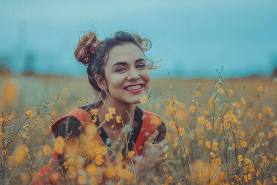 Mujer sonriendo entre las flores en el campo
