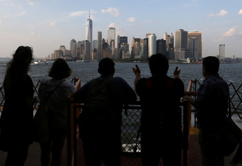 People view the skyline whilst riding the Staten Island Ferry in New York