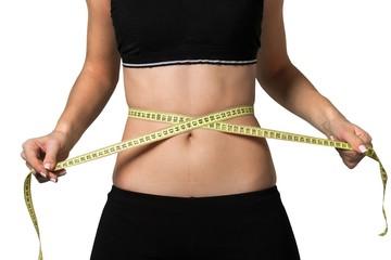 Female fitness model holding a tape measurer around her waist -