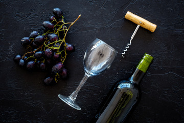 Composition with wine. Red wine bottle, bunch of grapes, corkscrew, wine glass on black background top view