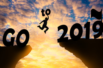 Happy new year Silhouette sunset background. A man jumping over cliff and jump between 2018 and 2019 years. Photo Silhouette and new year  concept idea.