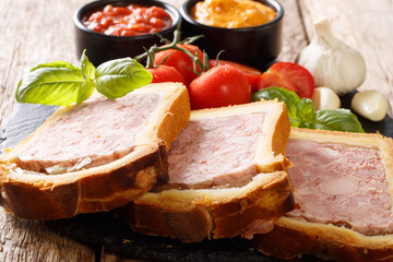 Meat terrine, pate with spices, garlic served with vegetables and sauces close-up. horizontal