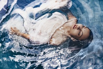 close up portrait of beautiful woman lying in water with fabric. Fashion concept