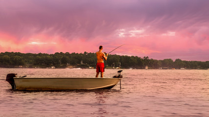 A man is fishing under sunset