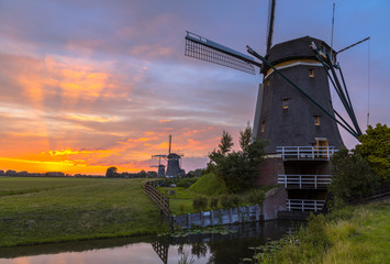 Wall Mural - Three Wooden windmills in a row at orange sunset