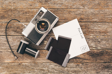 Vintage camera on weathered background with film, postcard, and film canisters