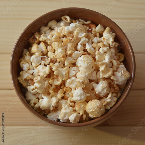 Popcorn in a brown ceramic bowl on a wooden table. Top view ...