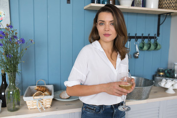 Woman drinking wine in the kitchen.