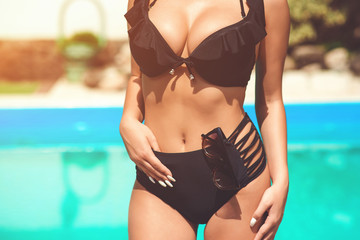Sexy woman in black bikini in swimming pool. Beautiful woman wearing swimsuit. Closeup of woman's body in sexy bikini. Torso of luxurious woman. Big tits, biggest boobs, sexy breast, sexuality bra.Hot