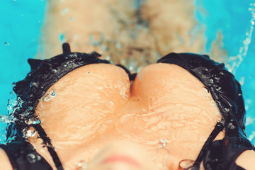 Image of woman's bare chest with water drops. closeup portrait of female sexy big wet breast. Female sexy breast xxl tits. Biggest boobs in black bikini. Big natural breast close-up. top view