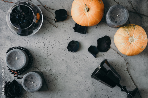 Halloween background, still life flat lay composition of black roses, candles, small pumpkins, dried branches and vintage wineglass over grey. Top view.