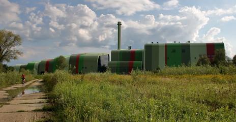 Kolorowy budynek spalarni śmieci w Krakowie, zarośnięta łąka przed nim, po drodze w betonowych...