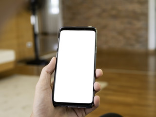 close up of man holding smartphone in hand, relax sitting and using smart phone with blank copy space white screen for graphic application or advertising in cafe or co-working space from top view.