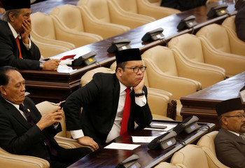 A parliament member listens as Indonesian President Widodo delivers a speech ahead of Independence Day in Jakarta