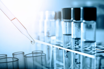 Dropping chemical liquid to test tube with lab glassware background, science or medical research and development concept.