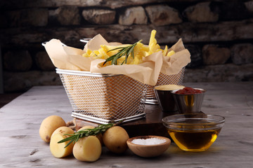 french fries, chips on wooden background with salt