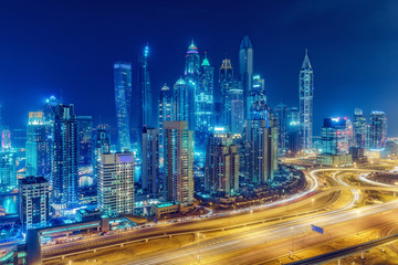 Scenic nighttime skyline of big modern city with illuminated skyscrapers. Aerial view of Dubai Marina, UAE. Multicolored travel background.