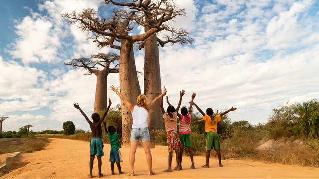 woman exult with black children and greating a baobab tree, concept of african united