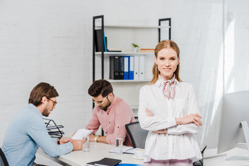smiling young businesswoman with crossed arms looking at camera and leaning back on table at modern office while colleagues working together on background