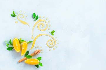 Honey dipper with decorative honey swirls and lemon slices on a white wooden background with copy space. Creative food photography from above. Painting with food concept