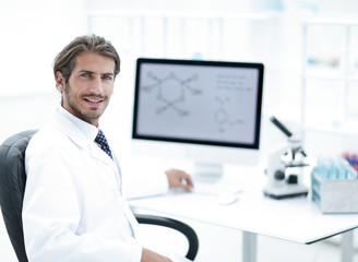 Male scientist sitting at table in laboratory