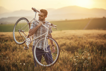 young man with retro bicycle in sunset on the road, fashion photography on retro style with bike