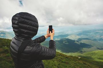 hiker enjoying the view and taking photos by the phone on mountain ridge. Carpathians, Ukraine