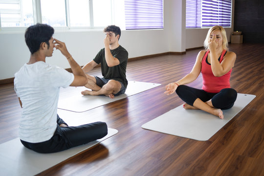 People practicing alternate nostril breathing technique with instructor at yoga class. Men and woman sitting in sukhasana yoga pose. Pranayama concept.