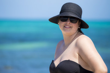 Portuguese woman with hat and black glasses with blue sea truquesa background.