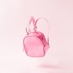 Pastel pink school bag floating. Surreal modern still life. Back to school minimal concept.