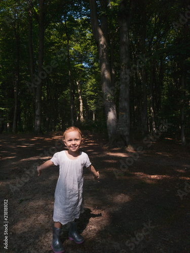 492092df3 Little girl into the forest smiling and playing. Alone in the woods ...