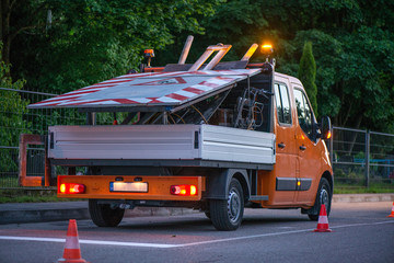 Car on side of road with warning lights. Road construction works. Traffic line painting. Painting white street lines on pedestrian crossing. Road cones with orange, white stripes standing on asphalt
