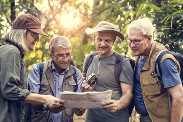 Group of senior trekkers checking a map for direction