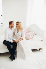 Portrait of beautiful couple of mom and dad embracing stomach and looking each other, touching face to face. Pregnant blonde woman in white smiling to her handsome husband, posing at stylish interior.