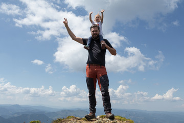 Father holding little girl on his shoulder while on top of the mountain. Sunny summer day. Freedom and parenting