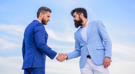 Sure sign you should trust business partner. Men formal suits shaking hands blue sky background. Business deal approved accepted by both partners. Entrepreneurs shaking hands symbol successful deal
