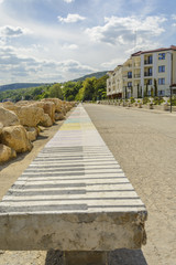 Walkway in the beach with hotel and a long bench with piano keys and a bright sky in Balchik, Bulgaria.