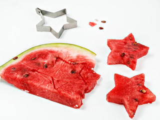 Figures of asterisks carved from a piece of watermelon on a white background